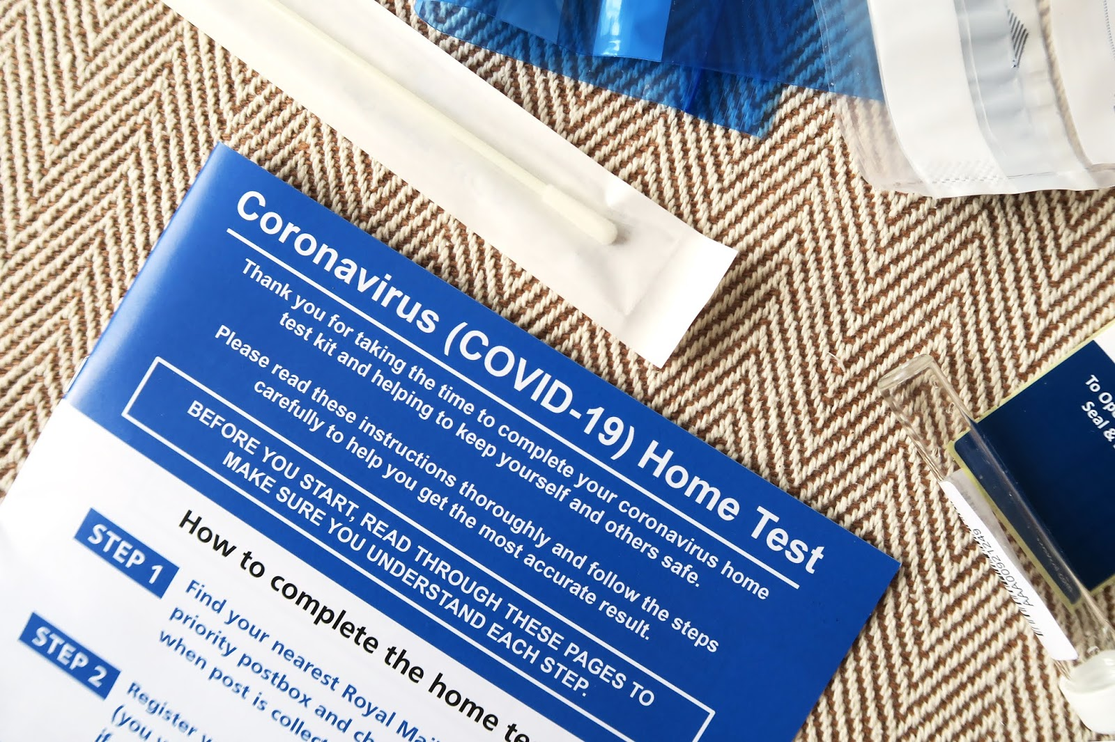 The contents of a UK coronavirus testing kit - including instructions, a swab, a small vial, and easy seal plastic bags