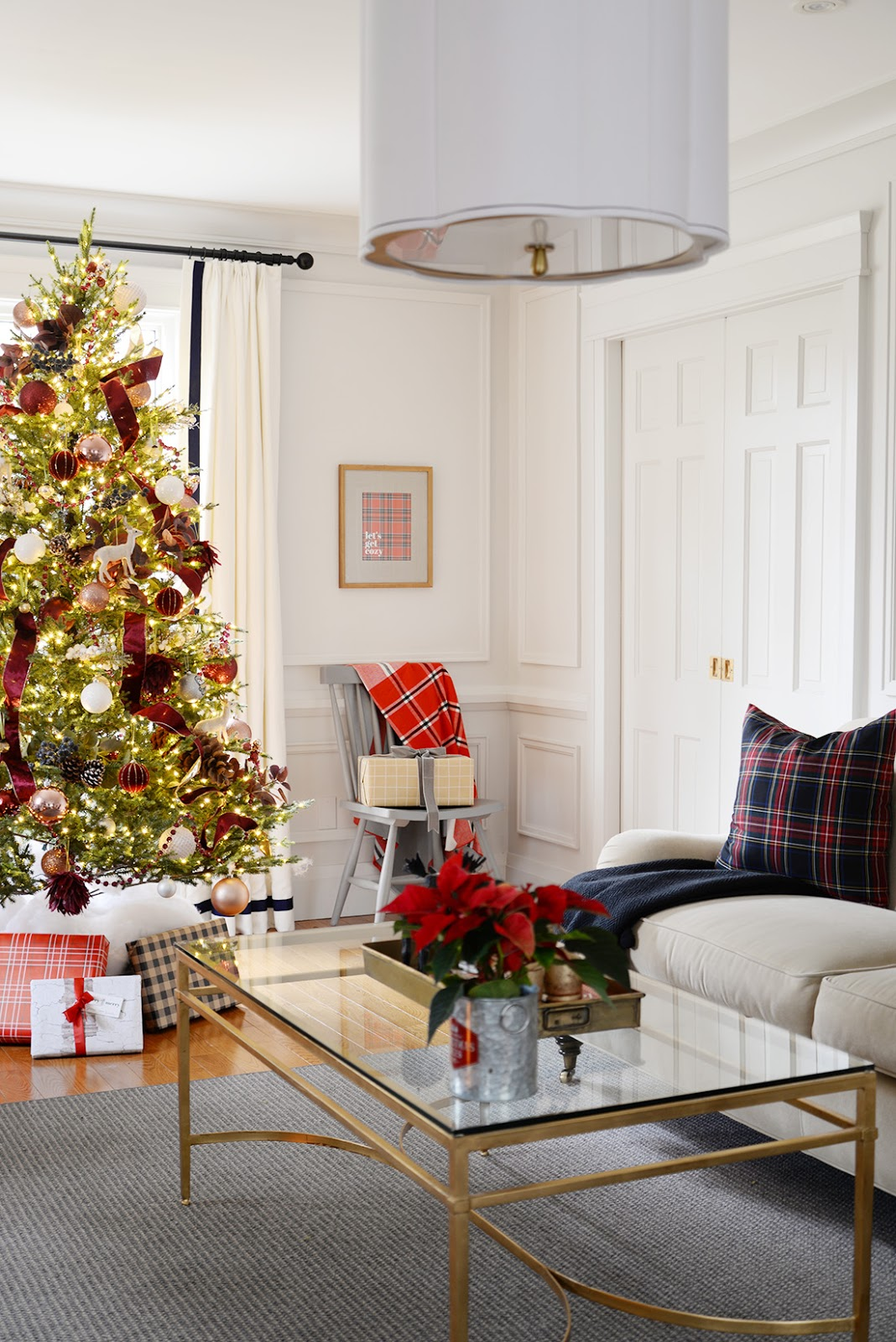 Living room decorated for Christmas with red and white Christmas tree. Canadian Tire mulberry collection Christmas ornaments. Plaid throw and tartan pillows