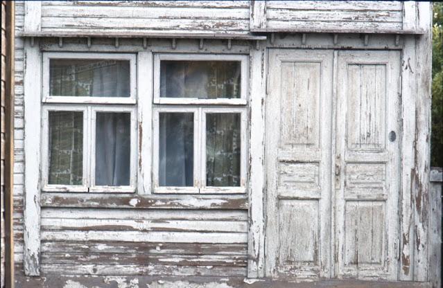 Vanhan puurakennuksen seinä, jossa on ikkuna ja ovi. Seinän maalipinta hilseilee.