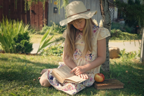 Young girl reading on the grass
