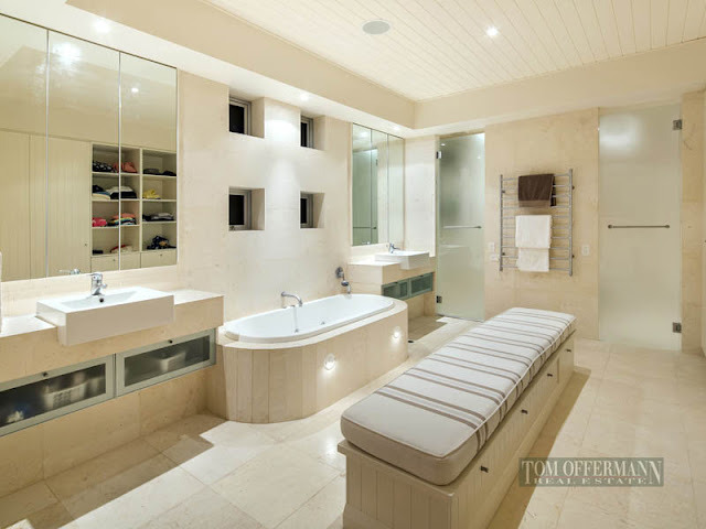 Photo of huge modern bathroom with sitting bench in the middle