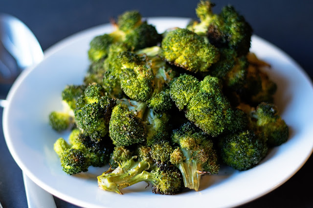 The roasted broccoli on a white plate.