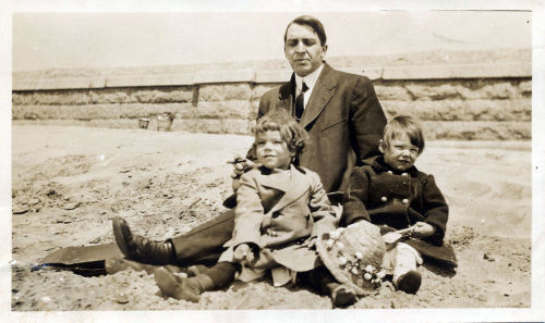 man with two children on a beach in 1911