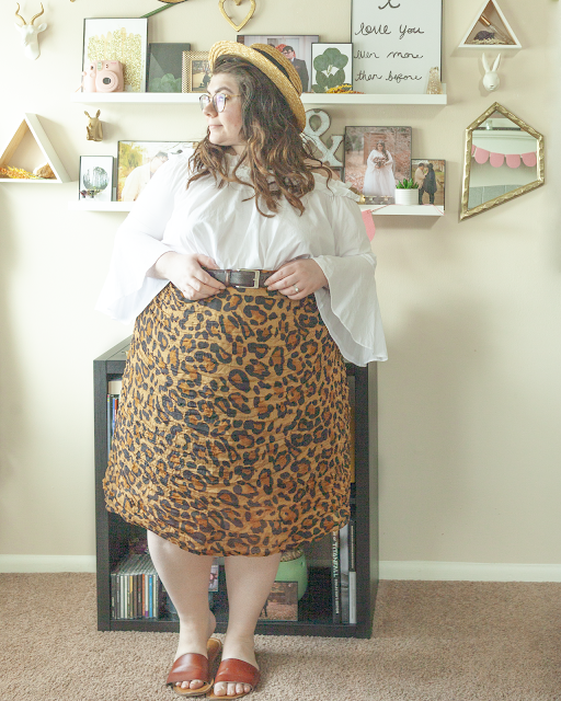 An outfit consisting of a straw boater hat, a white off the shoulder blouse with bell sleeves tucked into a brown leopard midi skirt and brown slide sandals.