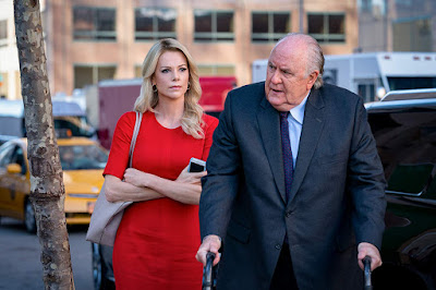 "Megyn Kelly (Charlize Theron) and Roger Ailes (John Lithgow) walk together on a New York City street in ""Bombshell."""