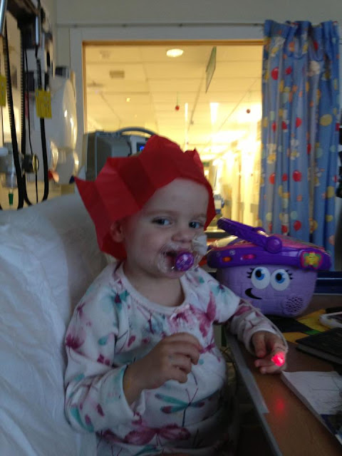 A little girl wearing a Christmas cracker hat, whilst in a hospital bed