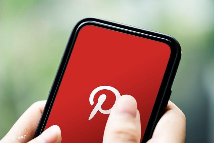 Mão segurando celular no Pinterest.