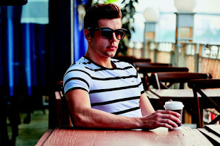 Male wearing sunglasses sits at a cafe table with a latte in hand
