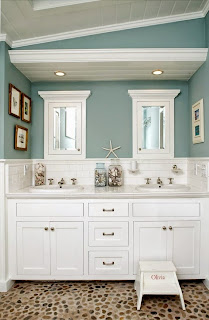 cool powder room with white vanity cabinets and nautical decorating items below mirror under yellow recessed lights
