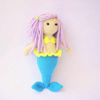 Colorful crochet amigurumi mermaid with violet hair and blue tail