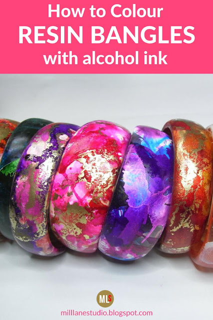 Row of brightly coloured alcohol ink bangles in shades of pink, red, purple, orange and green.