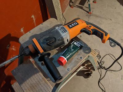 Verstaubter AEG Powertools Bohrhammer mit Meißel neben Metabo Spezialfett auf Leiter