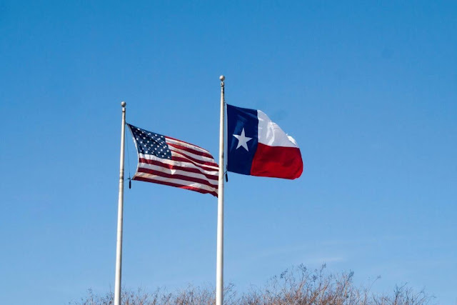 Houston to Austin Drive: American and Texas flags flying