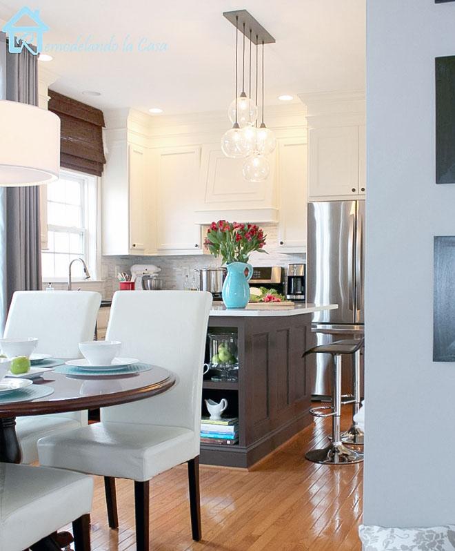 A kitchen makeover with white cabinets and dark kitchen island.