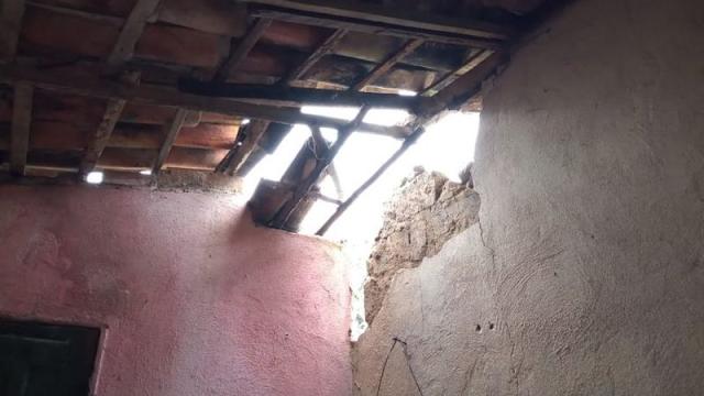 A imagem mostra uma foto de um telhado com telhas quebradas e uma parte da parede faltando devido aos tremores de terra. É uma casa com paredes rosas e brancas, as telhas são marrons e há uma estrutura de madeira por baixo.