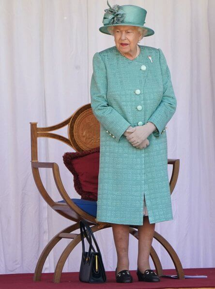 Queen is wearing a Stewart Parvin outfit, plus a floral silk dress with pleated hem detail, in shades of jade grey and dusty pink