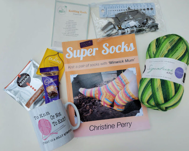 An orange book on a cream background surrounded by a mug, tea and coffee bags, a pack of knitting accessories, a purple pin badge and a ball of green and yellow striped yarn