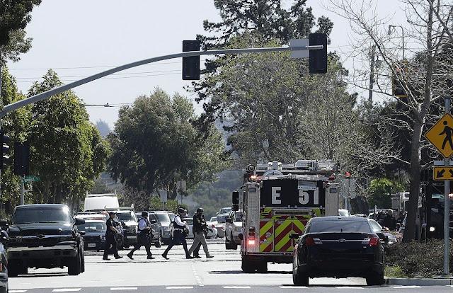 Foto na rua cheio de carros entre eles viaturas da policia e policiais indo até o local