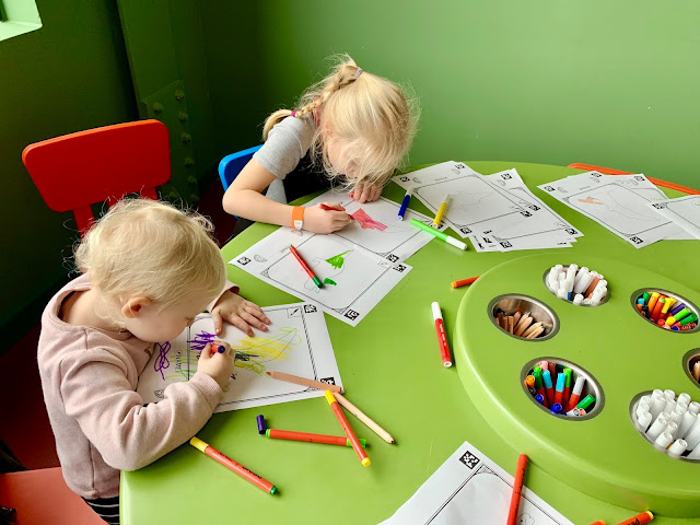 Children sitting at a school colouring in after finding out which primary school they have been given a space at