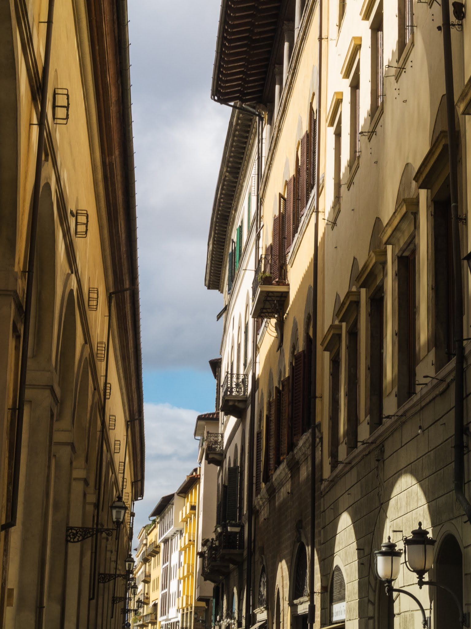 Sunlight shining on the buildings on a narrow street in Florence.
