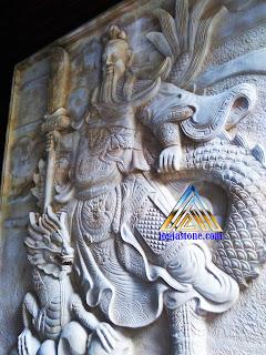 ukiran relief dari batu alam, batu putih atau juga biasa disebut batu paras jogja yang bermotif gambar  dewa kwan kong