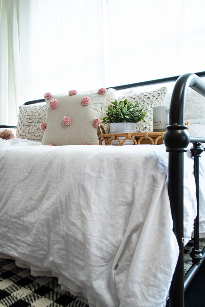 vintage inspired iron daybed with cozy pillows and throws