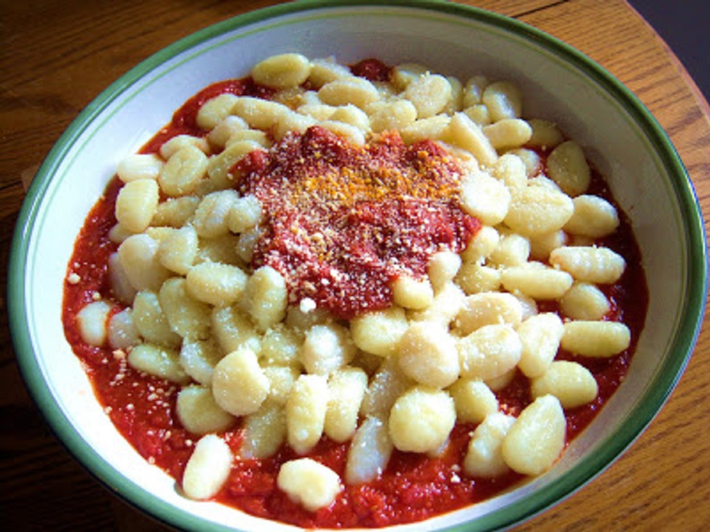Hand made potato pasta called gnocchi using mashed potatoes and flour with cheese and tomato sauce on top.