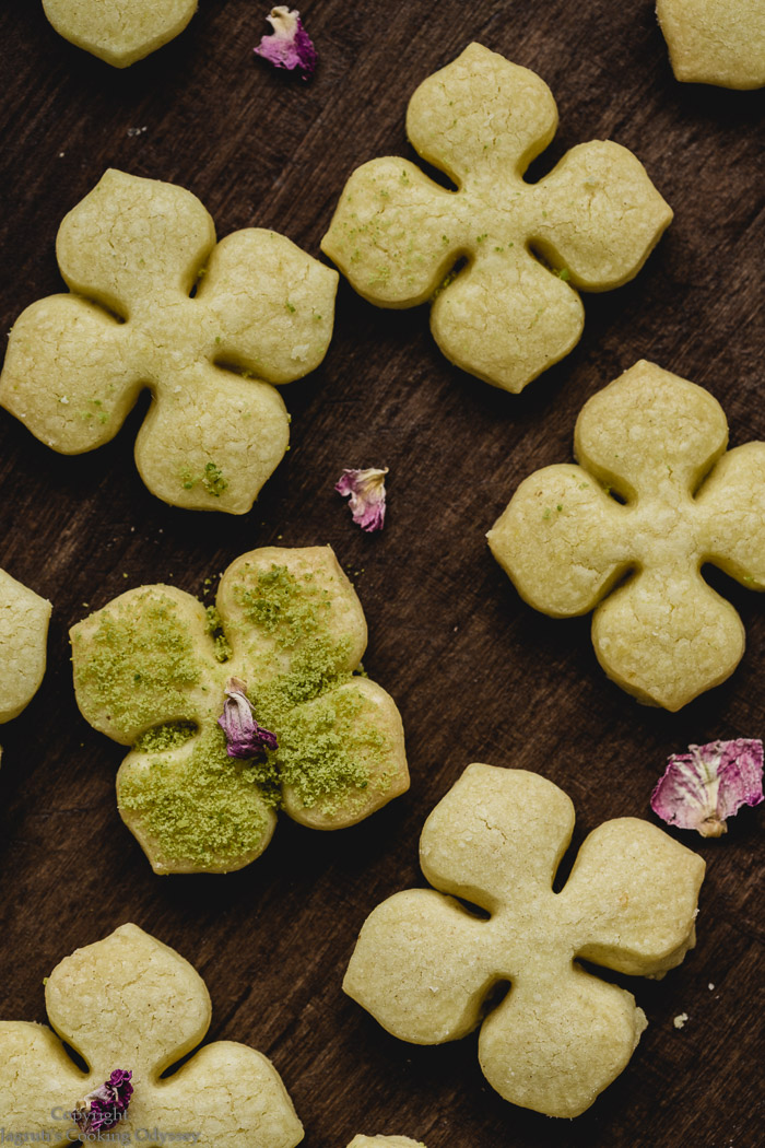 pale yellow saffron shortbread served in a metal tray, red rose petals are sprinkled over