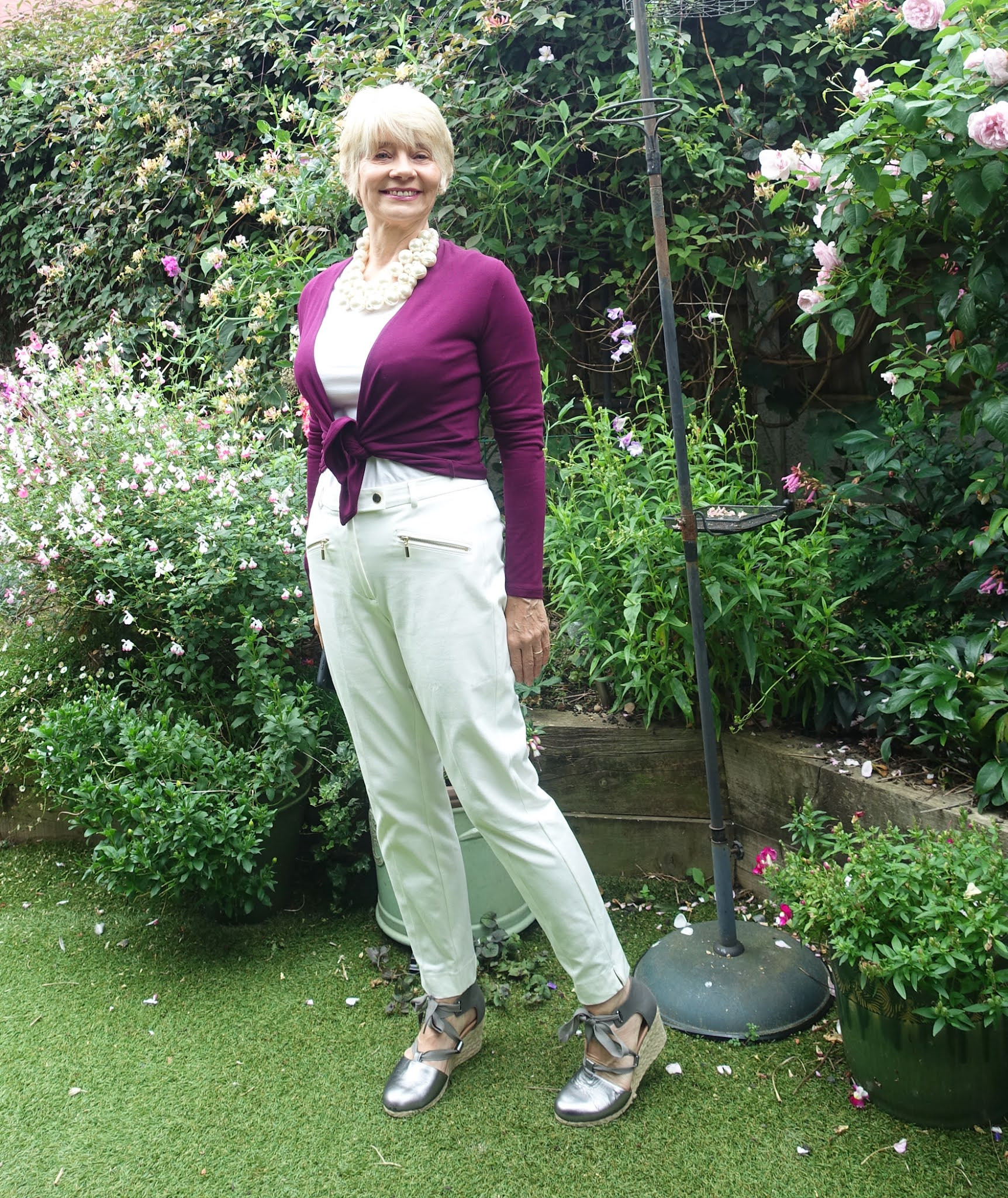 Gail Hanlon from Is This Mutton in high summer garden, wearing all-white with a Beetroot wrap and gunmetal wedges,