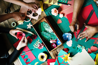 Made for community - several sets of hands working on colourful crafts together