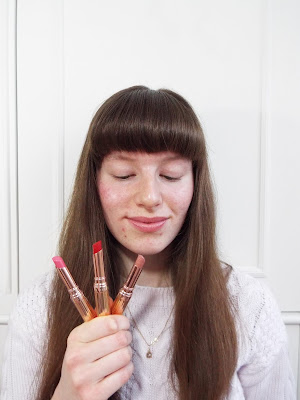 Ellie holding up an array of pretty pink, red and nude lipsticks, in gold packaging, smiling and thinking happily of their makeup memories