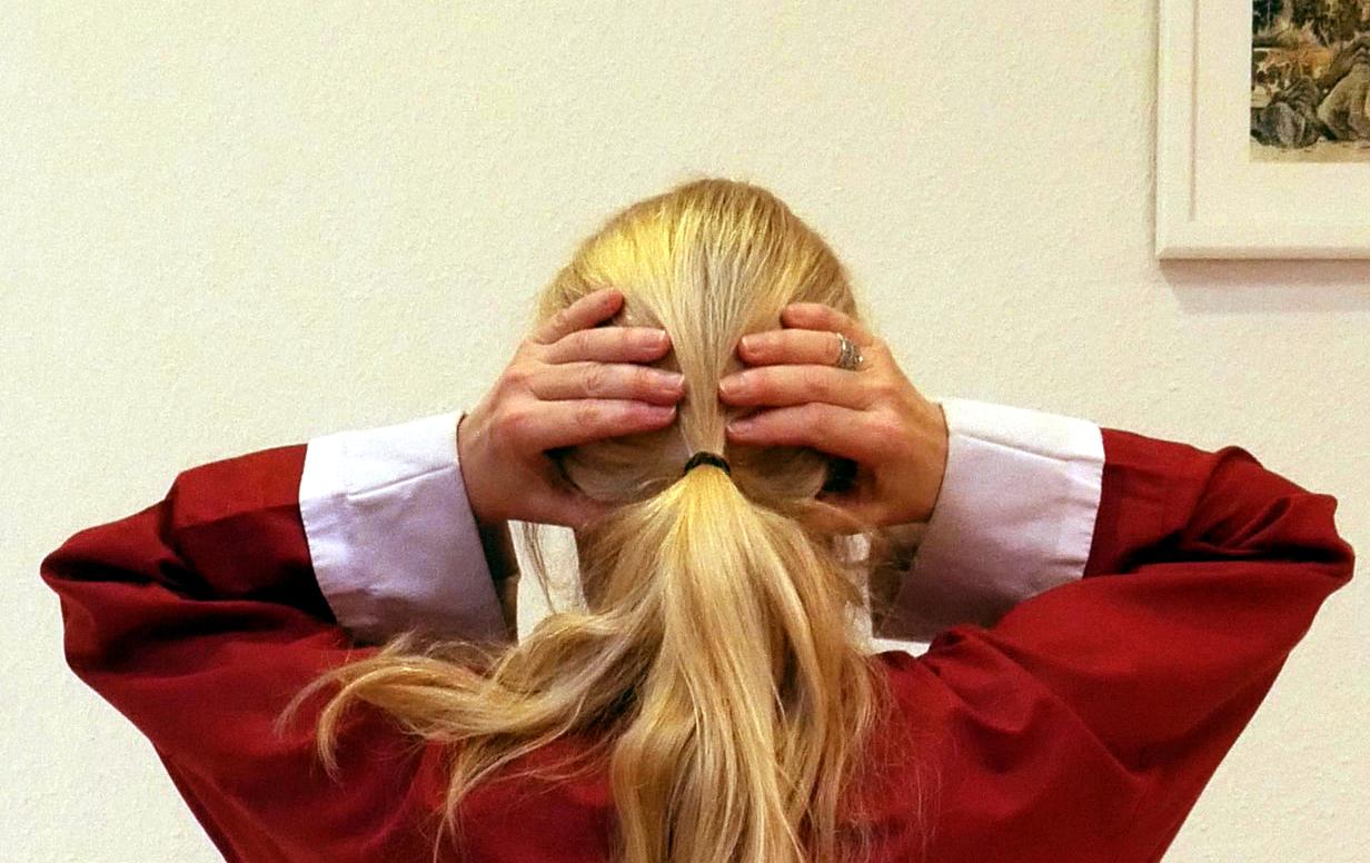 blonder Hinterkopf mit aufliegenden Händen