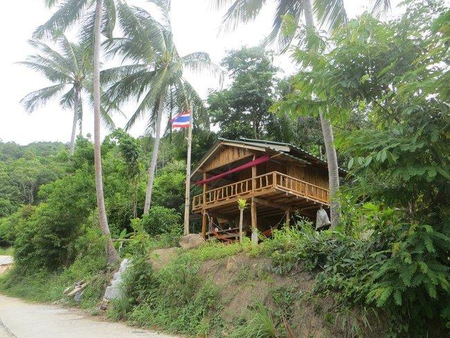 Маленький деревянный домик с тайским флагом