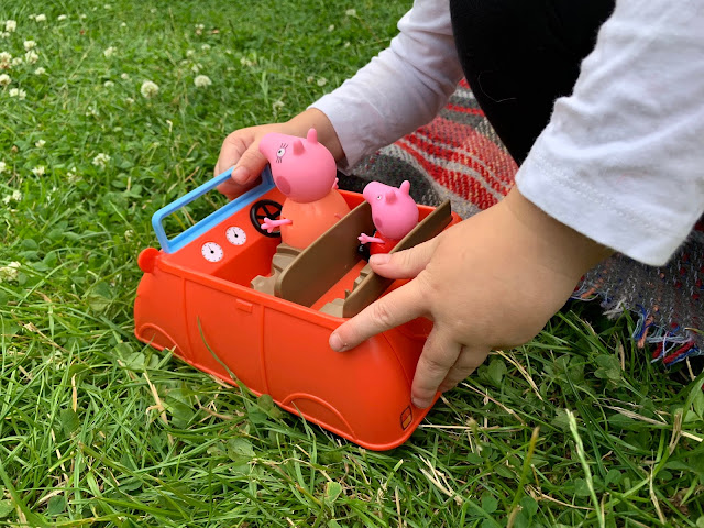 Toddler hands pushing the big red car along on grass