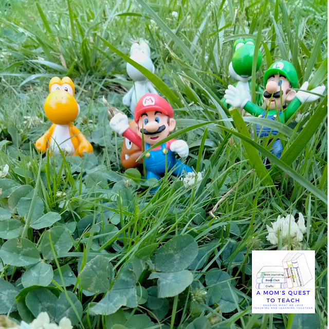 A Mom's Quest to Teach logo; Wordless Wednesday: Video Game Fun; Super Mario toys in grass