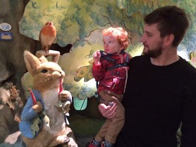 Daddy and toddler looking at Peter Rabbit figure