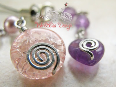 Close up of wire wrapped charms with cracked glass and amethyst, pearl, Swarovski Crystal and metal charm