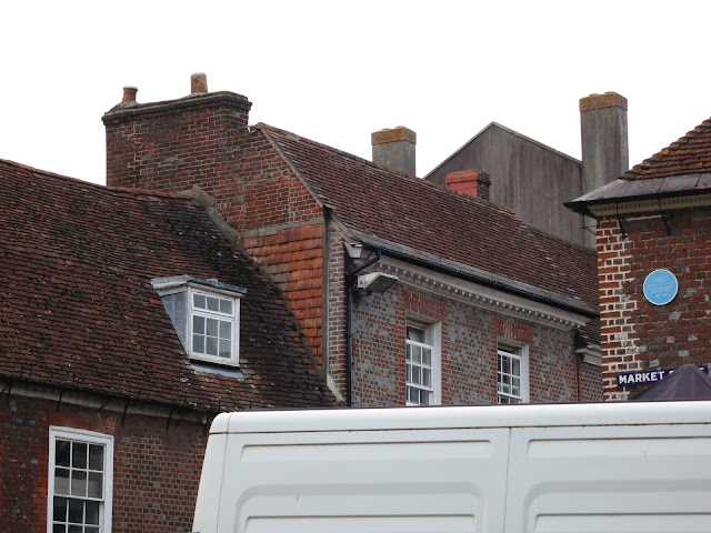 The tops of buildings roofs- upstairs windows, market stall - and the roof of a white van.
