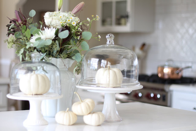 neutral fall decor white pumpkins flowers cake pedestals glass cloches
