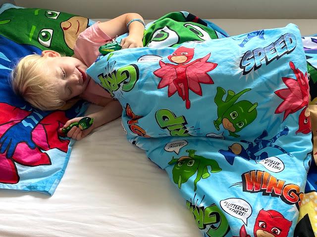 Child in bed with PJ Masks duvet set showing the underside