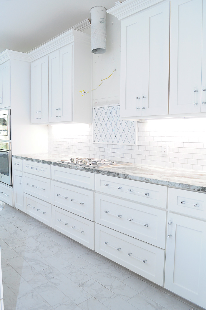 White shaker kitchen cabinets with lucite pulls and thassos reflection marble tile backsplash.