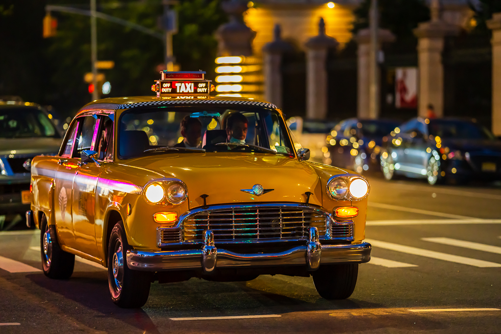 a photo of a classic car new york city taxi at night