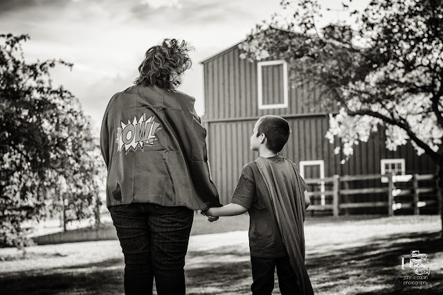 stunning black and white image of a brother and sister in front of a barn wearing superman capes