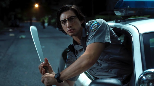 adam driver leans out a car window with a machete