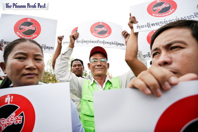 People hold signs during an anti-union law protest in front of Phnom Penh's National Assembly earlier this year. Hong Menea