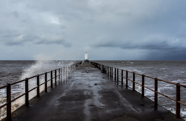 Photo of spray from the massive waves being blown over the pier