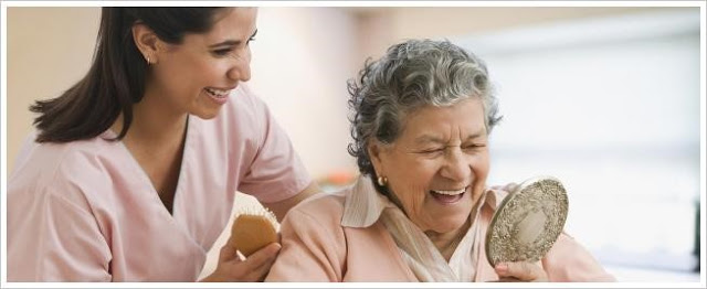 Home caregiver providing grooming assistance to senior adult woman