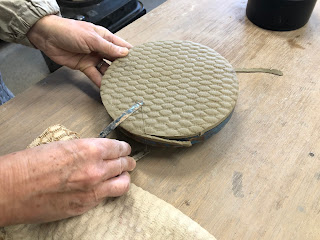 布で模様をつけた粘土をロクロに載せて丸く切っている写真