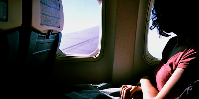 "Featured in the article: ""6 Tips To Get Over Flight Anxiety And Relax On A Plane"".  Taking a deep breath during flight, passenger, airplane, relaxation technique, beating anxiety"