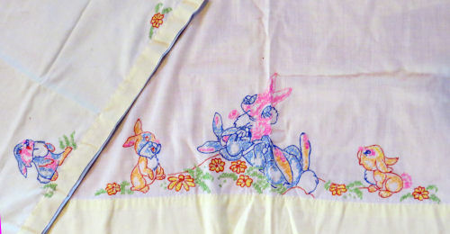 crib sheet edge with embroidered rabbits
